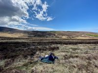 Lone hiker on a picnic blanket in the heather